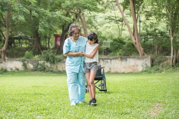 병원 정원에서 손녀와 휠체어에 노인 할머니