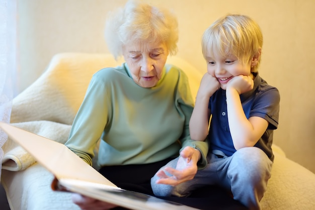 Elderly grandmother and little grandchild looking family photos album. grandma and grandson.