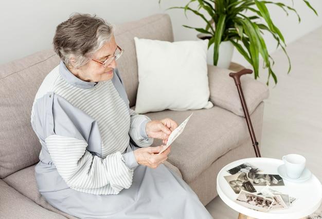 Пожилая бабушка смотрит на старые фотографии