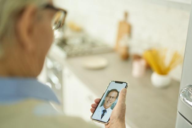 ビデオ通話でセラピストに相談するおじいちゃん