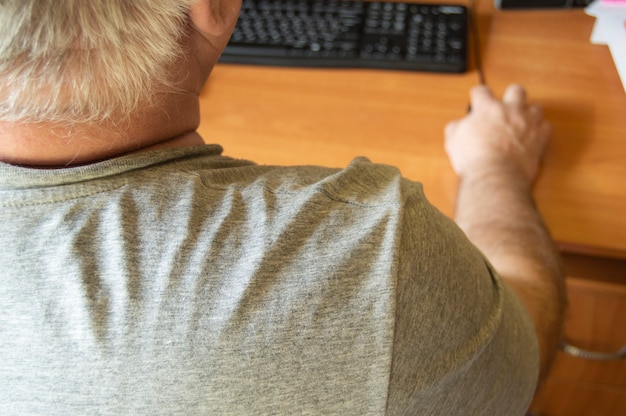 An elderly gray-haired man uses a computer mouse