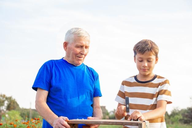 회색 머리의 노인과 십대 소년이 목공 도구를 들고 테이블에 서 있습니다. 할아버지는 화창한 날 정원에서 못을 망치는 법을 손자에게 가르칩니다.