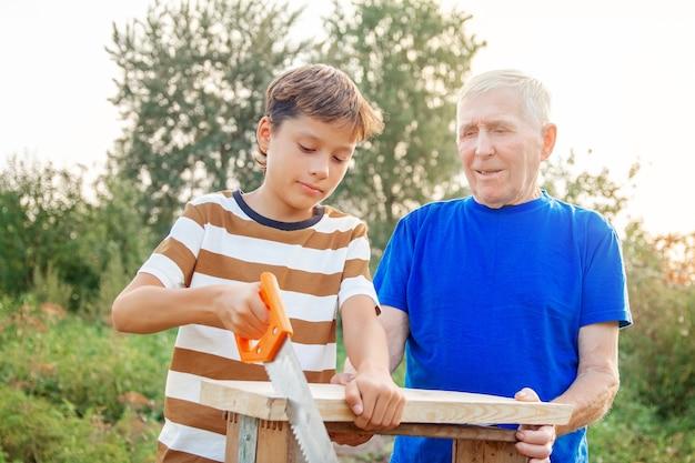회색 머리의 노인과 십대 소년이 목공 도구를 들고 테이블에 서 있습니다. 할아버지는 화창한 날 정원에서 나무 판자를 보도록 손자에게 가르칩니다.