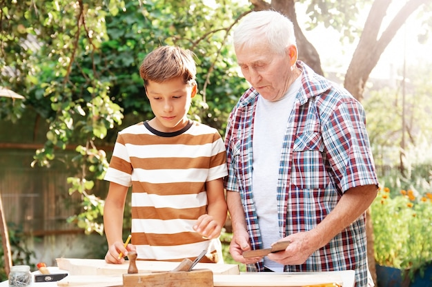 老人の白髪の年配の男性と10代の少年が道具を持ってテーブルに立っています。祖父は孫の大工仕事を教えています。