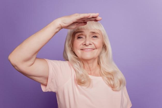 회색 머리 노인 여성이 보라색 배경에서 멀리 이마를 바라보고 손을 잡고