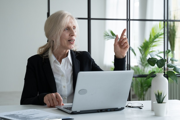 Elderly grayhaired woman uses a laptop comes up with an idea businesswoman working in a modern office