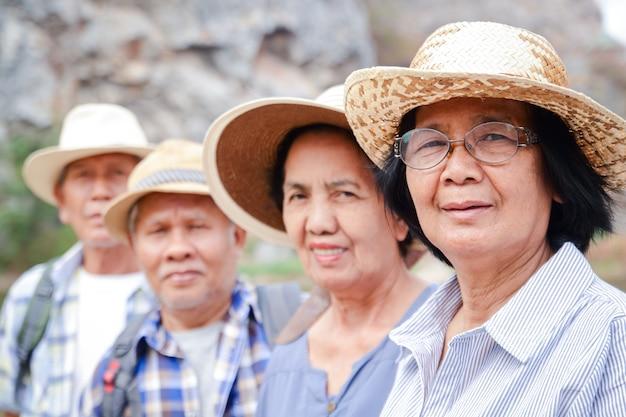Группа пожилых людей восхождение на высокую гору наслаждайтесь жизнью после выхода на пенсию. концепция сообщества пожилых людей
