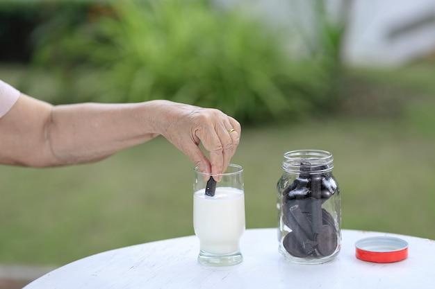 Пожилая рука окунает шоколадное печенье в стакан с молоком