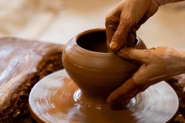 원에 흙 항아리를 만드는 도예가의 노인 손은 점토로 손으로 도자기를 만든다