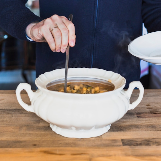 Elderly hands putting tasty soup on plate in kitchen