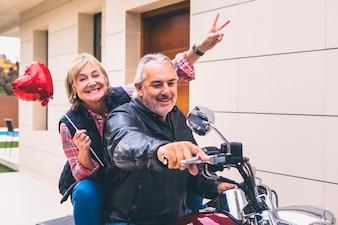 Elderly happy couple riding motorcycle
