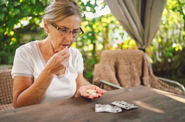 Пожилая счастливая старшая старуха в очках по рецепту принимает таблетки витаминов лекарств на открытом воздухе в саду. концепция образа жизни пожилых людей здравоохранения