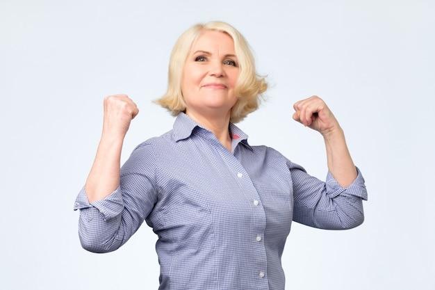 彼女の筋肉を示す自分を誇りに思っている高齢者の幸せな年配の女性
