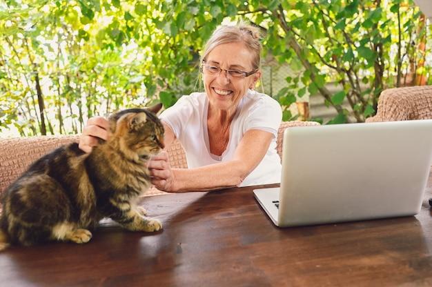 家の猫と年配の幸せな年配の女性は、庭の屋外のラップトップコンピューターでオンラインで動作するワイヤレスヘッドフォンを使用しています。リモートワーク