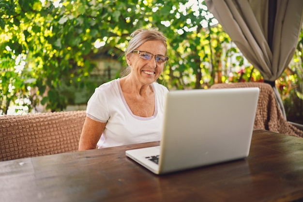 庭で屋外のラップトップコンピューターでオンラインで作業している年配の幸せな年配の女性。リモートワーク