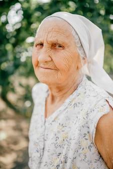 高齢者の幸せな女性の屋外のポートレート。しわの多い肌の顔を持つ老婦人。詳細な高齢者の顔の皮膚。田舎のライフスタイル。