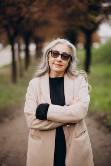 公園を歩く年配の幸せな女性