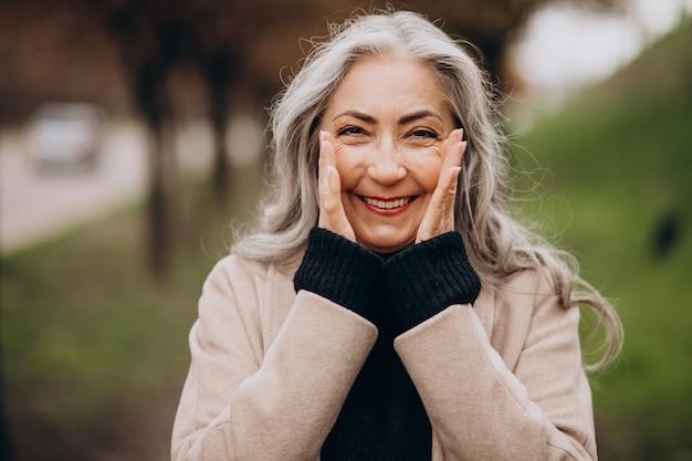 Пожилая счастливая женщина гуляет в парке
