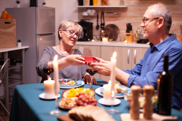 Elderly husband giving wife gift box during dinner. happy cheerful elderly couple dining together at home, enjoying the meal, celebrating their anniversary, surprise holiday