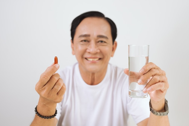 手にビタミン/オメガ3を持つ老人。