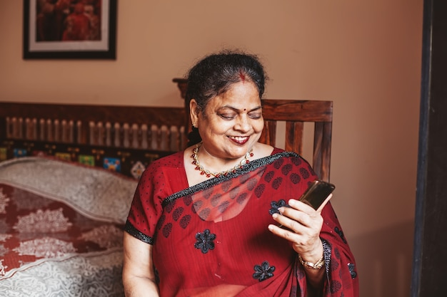 Elderly indian woman using her phone to connect over video call