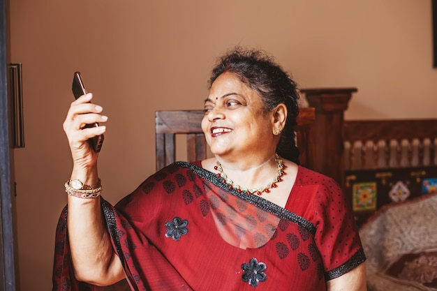 Elderly indian woman using her phone to connect  with her family