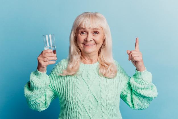 파란색 배경에 격리된 순수한 미네랄 워터 포인트 손가락 카피스페이스 한 잔을 들고 있는 노부인