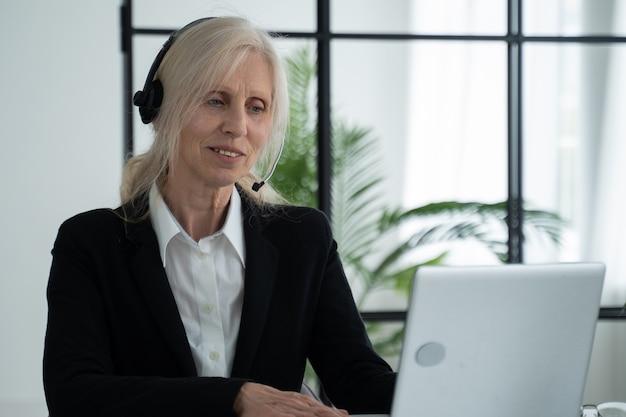 Пожилая женщина в гарнитуре разговаривает по видеоконференции, проводит видеоконференцию с помощью ноутбука в офисе