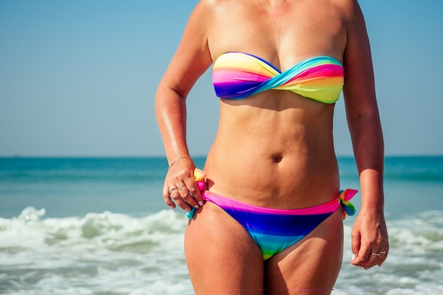 An elderly lady is resting on the beach. beautiful and colorful bright swimsuit on the flabby and old woman body on the beach.