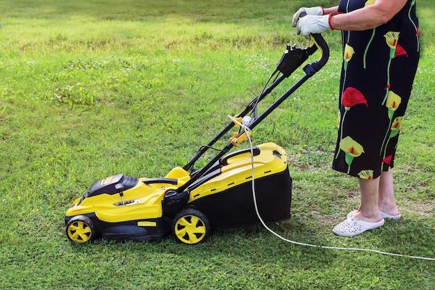잔디를 깎기 위해 전기 깎는 기계를 밀고 있는 할머니