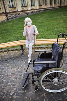 Elderly lady putting hand on a walking stick while sitting on the bench in medical mask and talking on the phone
