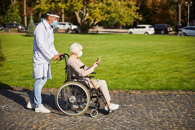 Elderly lady sitting with a smartphone in hands while a medical worker in protective shield pushing her wheelchair