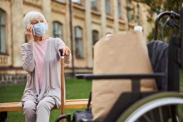 걷는 막대기가 야외에 앉아 전화로 이야기하는 동안 거리를 바라 보는 노인 여성