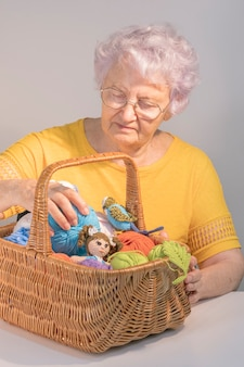 An elderly lady with a basket with balls of yarn and knitted toys. craft and diy concept. female hobby.