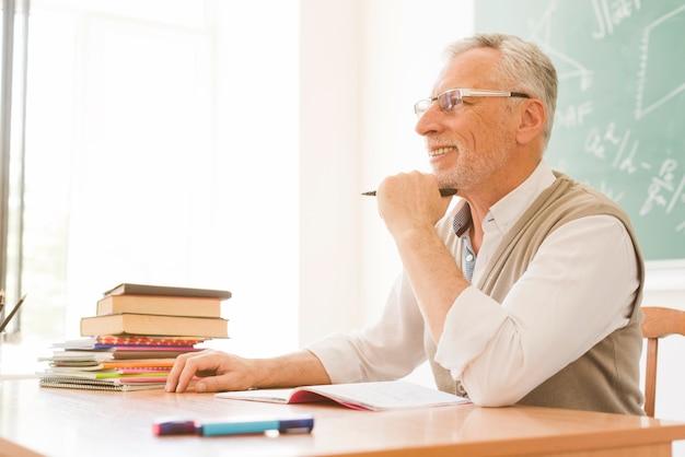 Пожилой преподаватель, сидя за столом в аудитории