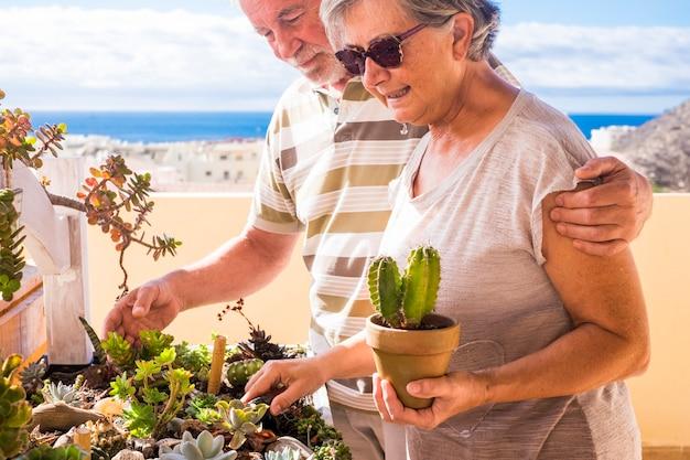 야외 테라스에서 집에서 작은 정원을 함께 즐기는 수석 백인 부부와 함께 노인 라이프 스타일