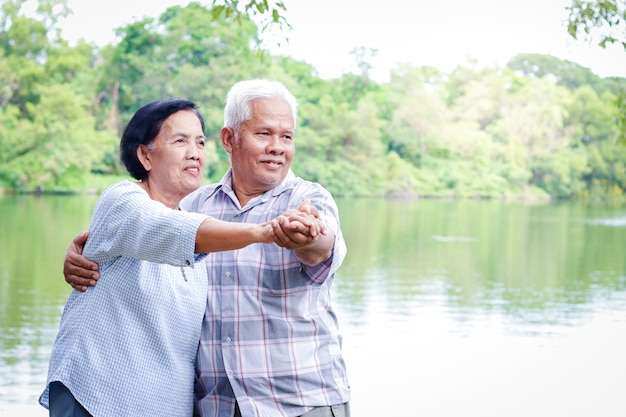 Elderly lovers holding hands dancing in the garden have fun in retirement life.