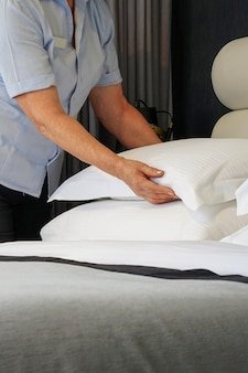 Elderly maid making bed in hotel room. housekeeper making bed