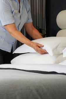 ホテルの部屋でベッドを作る年配のメイド。ベッドを作る家政婦