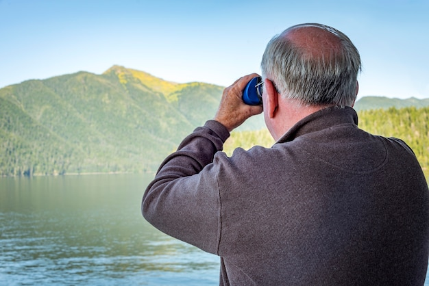 Elderly male on a cruise ship looking though a binoculars