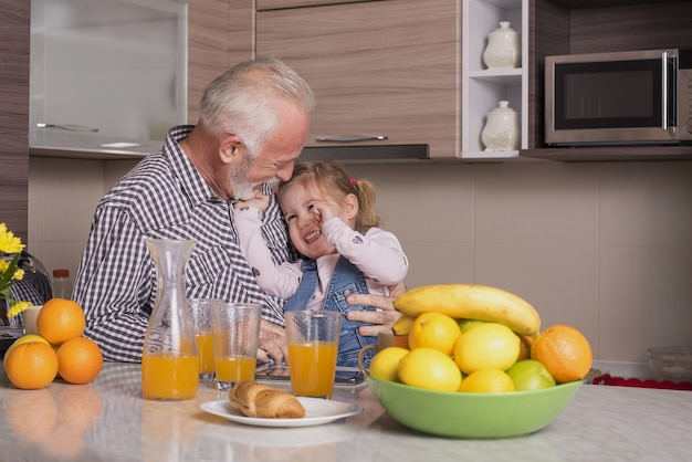 Elderly male and his adorable granddaughter drinking fresh orange juice and having fun in a kitchen