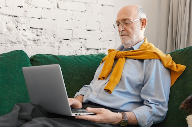 노트북에 집에서 무선 고속 인터넷 연결을 사용하여 대머리와 수염을 가진 노인 남성. 소파에 휴대용 컴퓨터에 비즈니스 뉴스를 읽고 심각한 집중된 성숙한 사업가