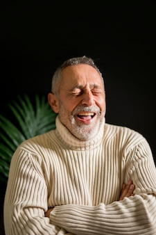 Elderly male with crossed arms laughing