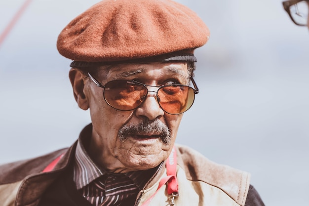 Un maschio anziano con gli occhiali che guarda da parte
