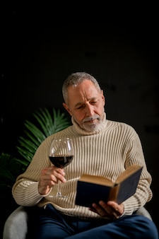 Elderly male with wine reading book
