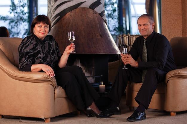 Пожилые мужчина и женщина пьют шампанское в романтической обстановке.