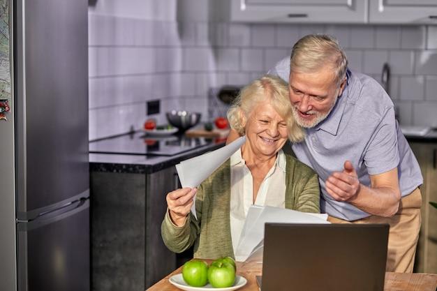 家族の1か月の予算を一緒に管理している老人と女性、コンピューターバンキングアプリケーションを使用してポジティブな夫婦、話し合っているキッチンで請求書を数える