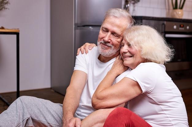 年配の男性と女性がスポーティーな服装で、自宅の床でヨガの後に休憩を取りながら座っています
