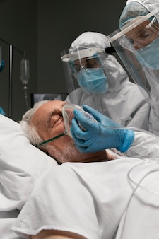 Elderly man breathing with a special equipment at the hospital