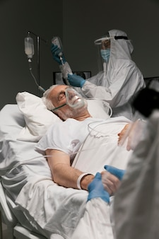 Elderly man breathing with a special equipment